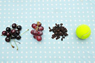 Small bunches of cherries and grapes, and a pile of raisins next to a tennis ball