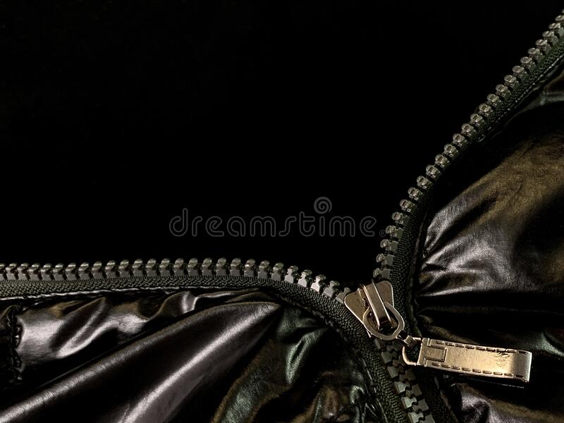 Background texture: zipper in a jacket on a black background. Opened lock on knit fabric royalty free stock photo