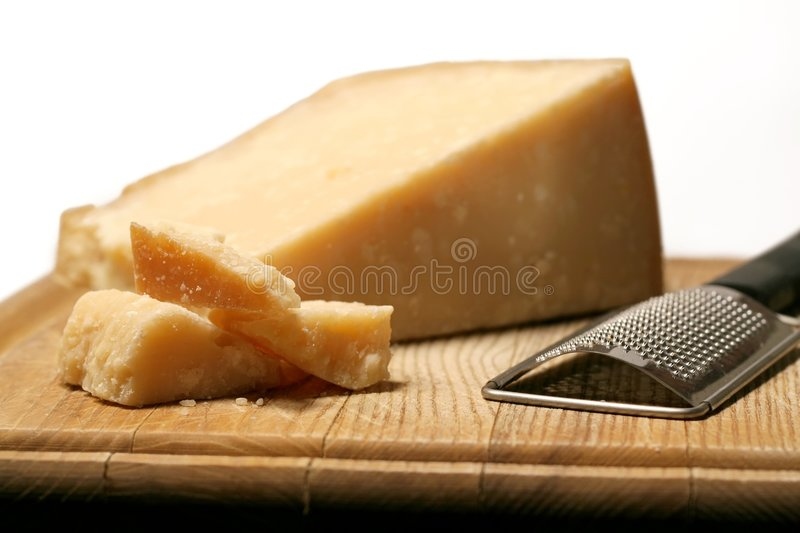 Block Of Cheese. Block of parmesan cheese with metal grater on wooden cutting board stock photos