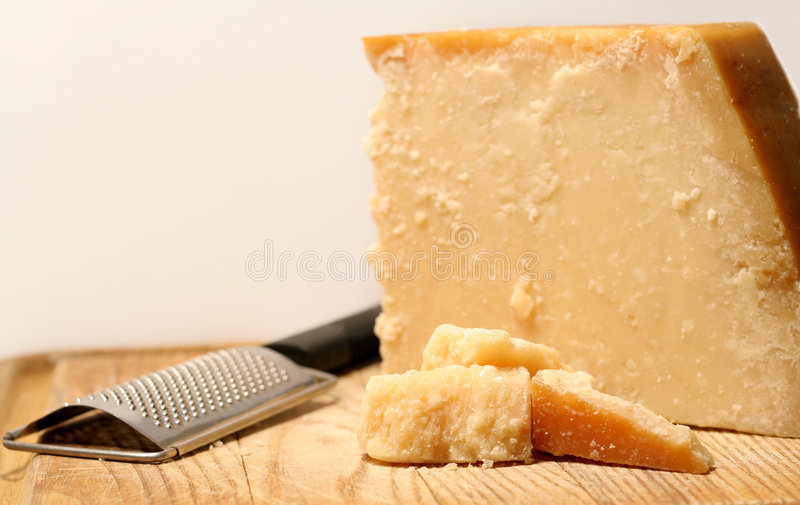 Block Of Cheese. Block of parmesan cheese with metal grater on wooden cutting board royalty free stock photos