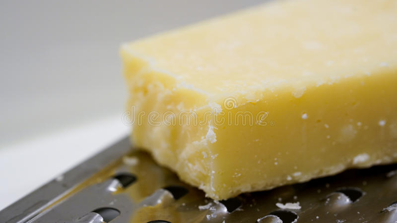 Cheese on a cheese grater. Close up of a block mozzarella cheese on a metal cheese grater, bright background stock photography