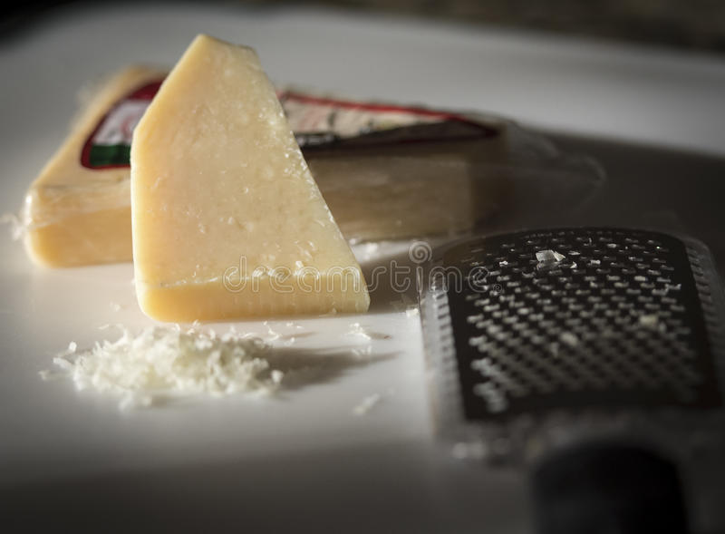 Cheese and Grater. White Cheese block and grater with grated cheese in front of cheese block. Italian food stock photo