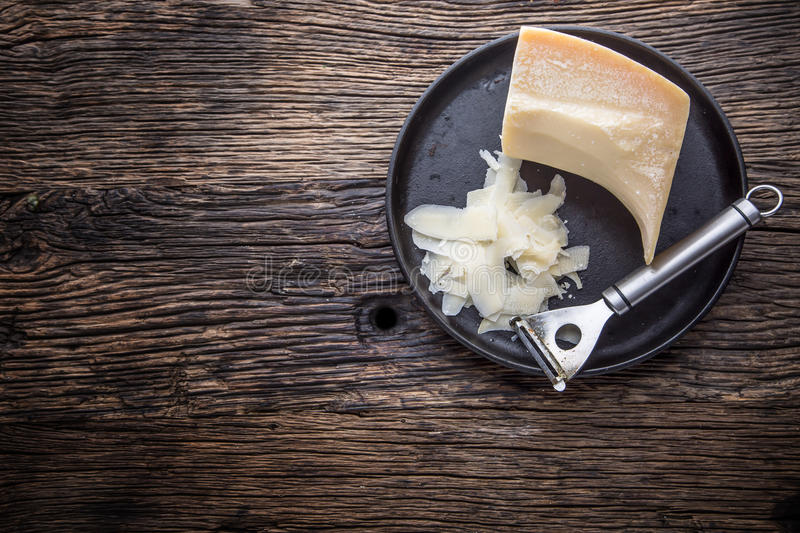 Cheese Parmesan . Parmesan cheese on old oak table with cheese grater.  stock image