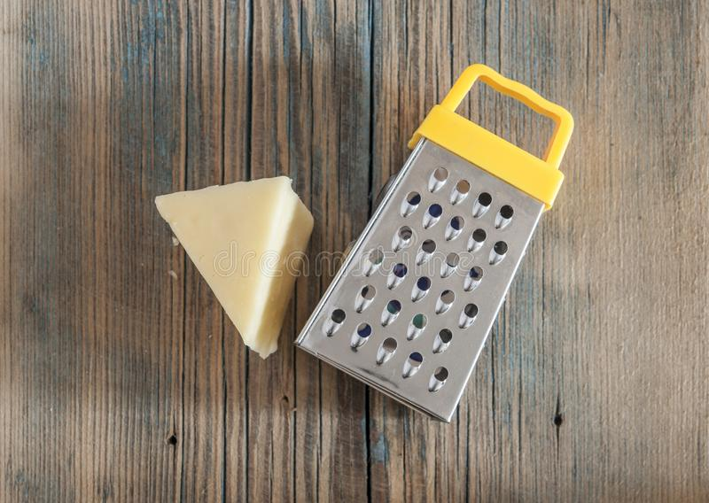 Steel grater and cheese on wooden board. Cheese and steel grater on a wood kitchen table royalty free stock photos