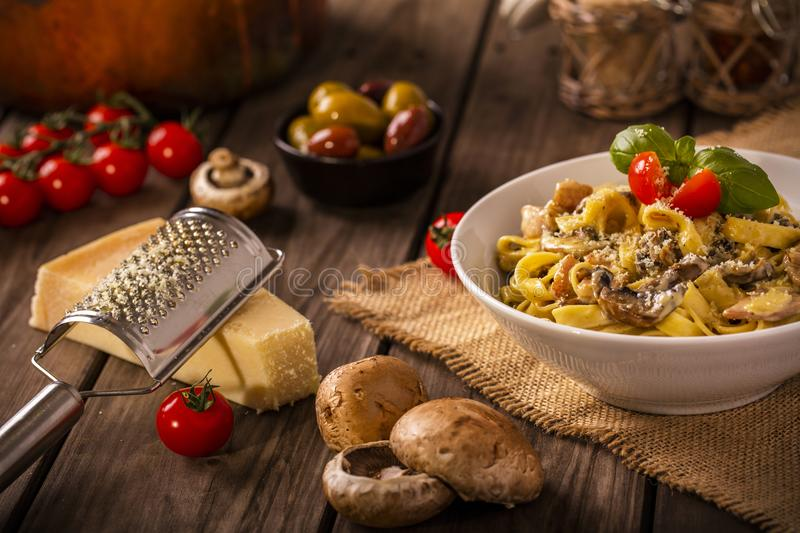 Chicken and mushroom pasta rustic. Chicken and mushroom tagliatelle shot on wood boards at an angle with a copper pot loose mushrooms vine tomato parmesan block royalty free stock photography