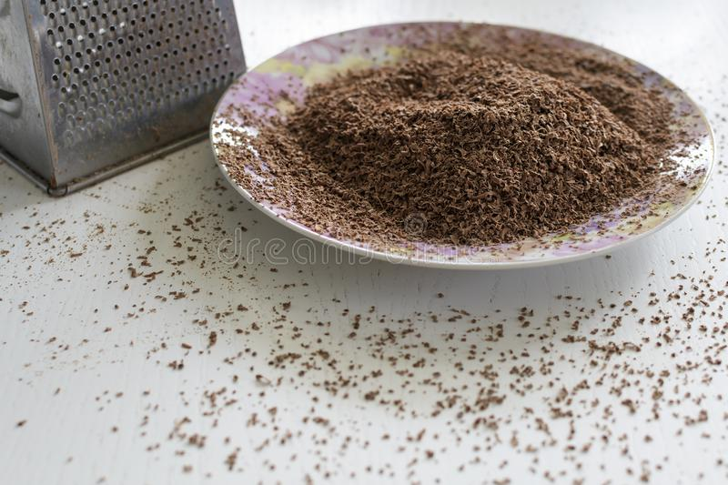 Chocolate grated on a fine grater. Lies on a plate royalty free stock photo
