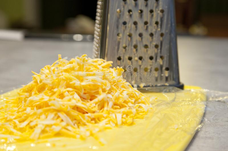 Close up shredded cheese. Pile of Shredded cheese beside a metal grater in the kitchen royalty free stock photo
