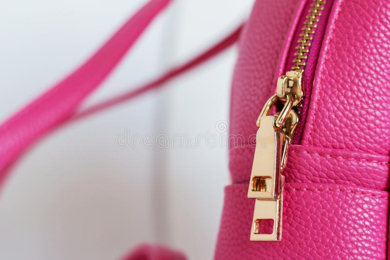 Golden color lock zipper on pink backpack. Close-up royalty free stock images
