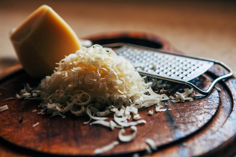 Grated cheese on a cutting board. Next to a piece of cheese and a grater. Grated cheese on a cutting board. Next to a piece of cheese and a grater stock image