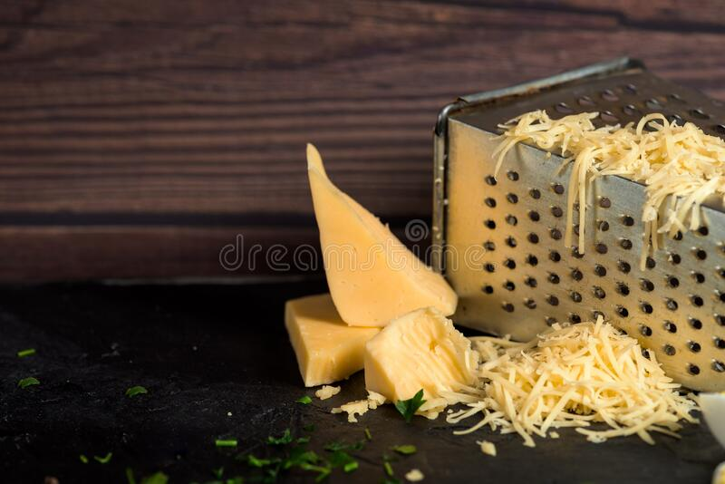 Grated cheese on a grater on a dark wooden background. close up.  royalty free stock images
