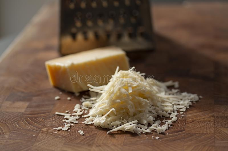 Grated italian parmesan cheese on wooden chopping board with a block of parmasan and a grater in the background. Close up photo. With selective focus royalty free stock photography