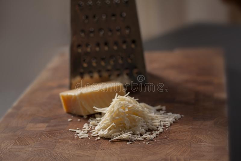 Grated italian parmesan cheese on wooden chopping board with a block of parmasan and a grater in the background. Close up photo. With selective focus stock image