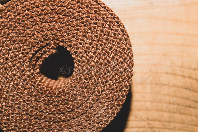 Industrial harness rolled up on a wooden table. working tool. Industrial harness rolled up on a wooden table. work tool, accessory, backdrop, background, canvas royalty free stock image