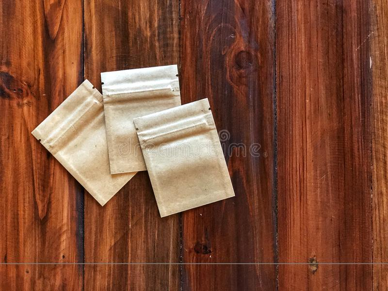 3 Kraft Paper zipper lock bag on the vintage wooden table. Empty packing bag for your product advertisement.Top view and copy space stock photo