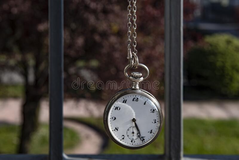 Lock down concept. Pocket watch and a park view on the background, corona virus lock-down concept stock photography