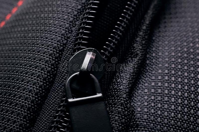 Lock and zipper on black fabric close up. Macro photo royalty free stock photography