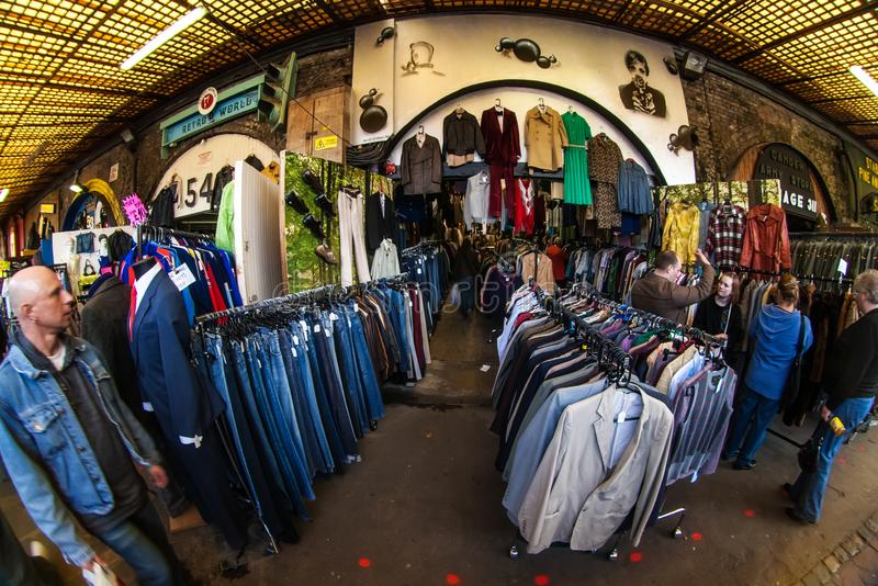 London, United Kingdom - March 31, 2007: Extreme wide angle fisheye photo, unknown shoppers checking clothes in one of many. Stalls at Camden Lock, famous flea royalty free stock photos
