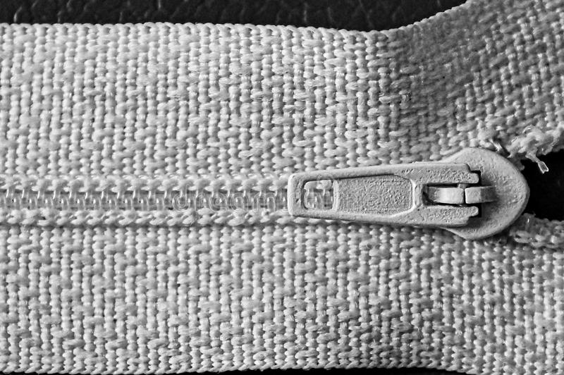 Part of a zipper with a lock on white cloth. Matter with a white lock and zipper stock photography