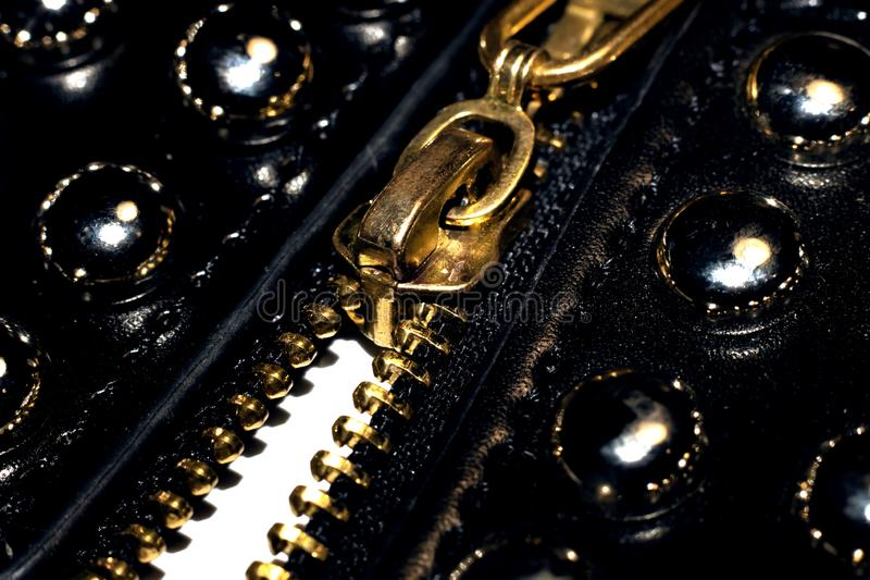 Zipper and lock on clothes close up. Metal yellow zipper and lock on black clothes close up royalty free stock image