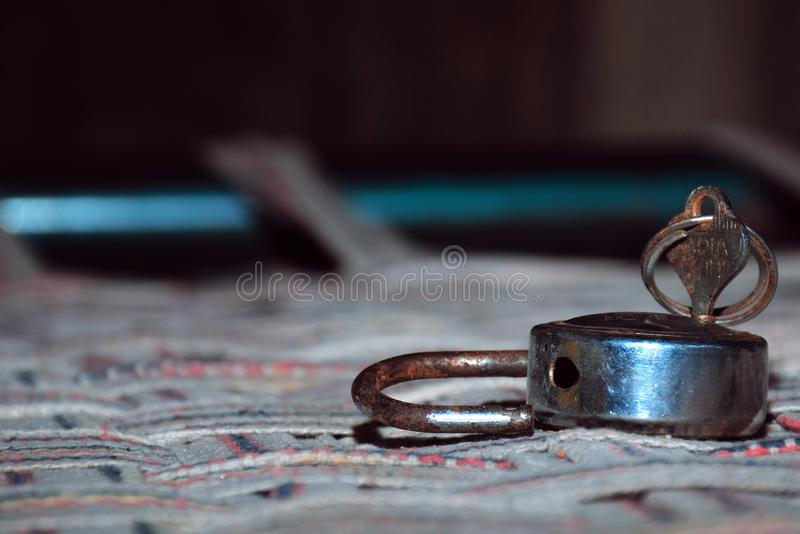 The old lock and key on abed of clothes with blur and black background 1. The old lock and key on abed of clothes with blur and black background stock photography