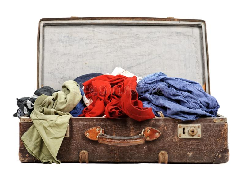 Old suitcase full of clothes. Isolated on white background stock photography