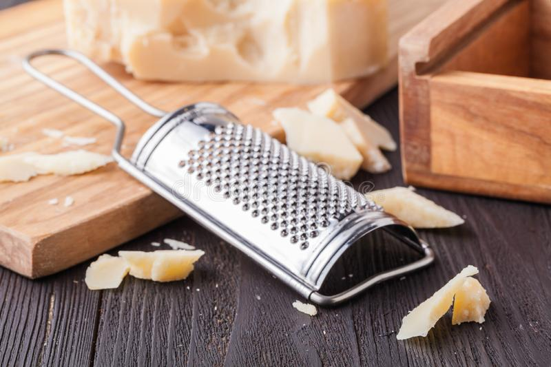 Parmesan cheese. Grated Parmesan cheese and Olive Wood Parmesan Cheese Grater royalty free stock image