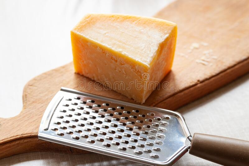 Parmesan cheese. A piece of cheese and grater on a wooden board. Fine grater for grating cheese. Traditional food stock photo