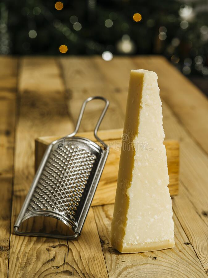 Block of parmesan cheese and grater. Photo of a block of parmesan cheese on a wooden table with grater in the background royalty free stock image
