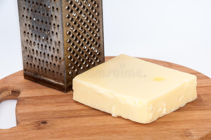 Piece of mozzarella cheese and metal grater on a kitchen wooden. Board royalty free stock photos