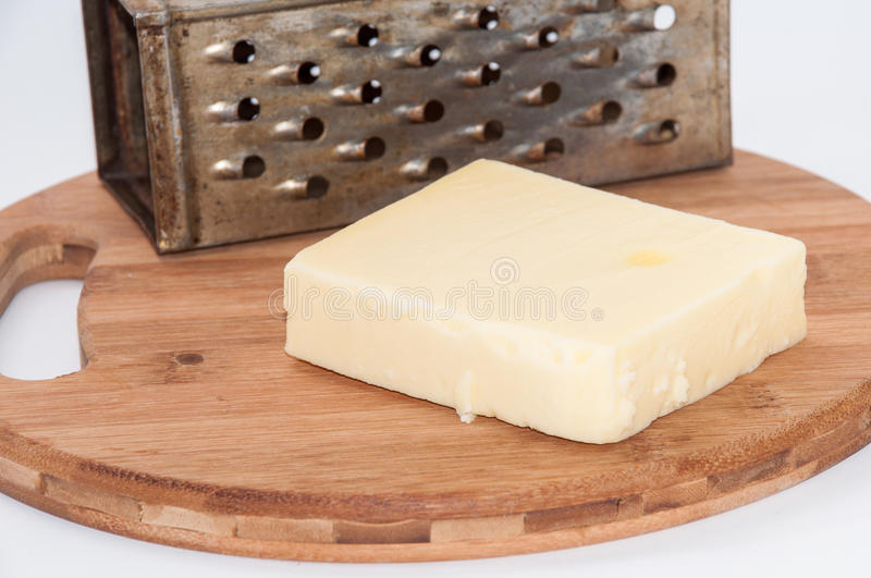 Piece of mozzarella cheese and metal grater on a kitchen wooden. Board royalty free stock images