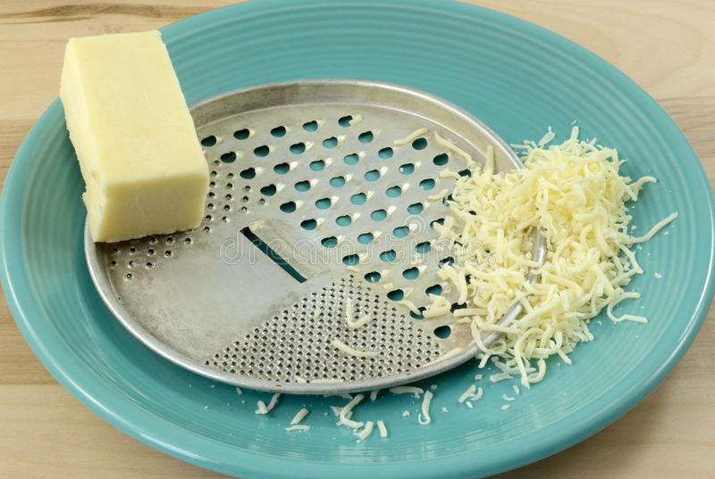 Retro vintage cheese grater with mozzarella cheese. Retro vintage cheese grater with block and shredded mozzarella cheese on blue plate stock photo