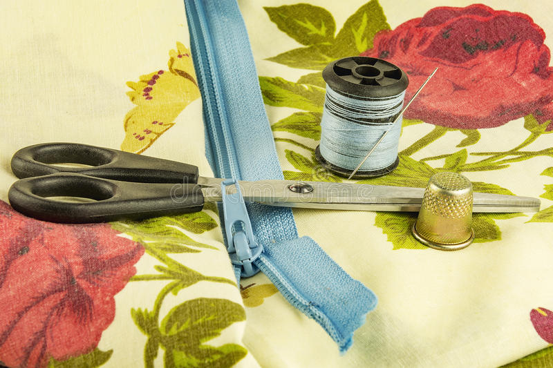 Scissors, zipper lock with a spool of thread and a thimble. On the surface of the cloth lie with thread and thimble and scissors lock zipper royalty free stock photography