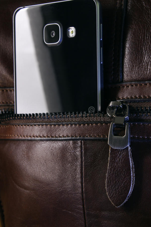 Smartphone in a pocket with a lock. Modern smartphone in a pocket brown bag close-up royalty free stock photography