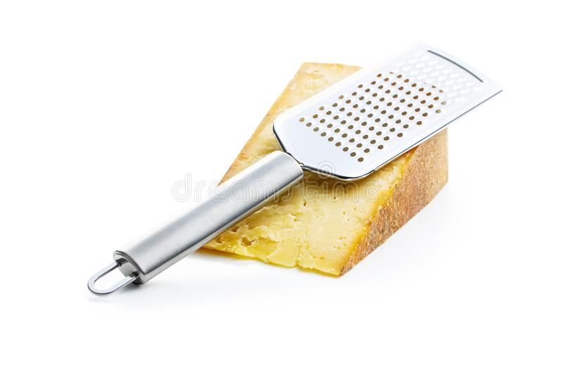 Tasty cheese block and cheese grater. Isolated on white background stock photo