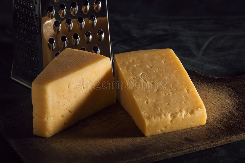 Two pieces of cheese and grater on a board against a dark background.  stock images