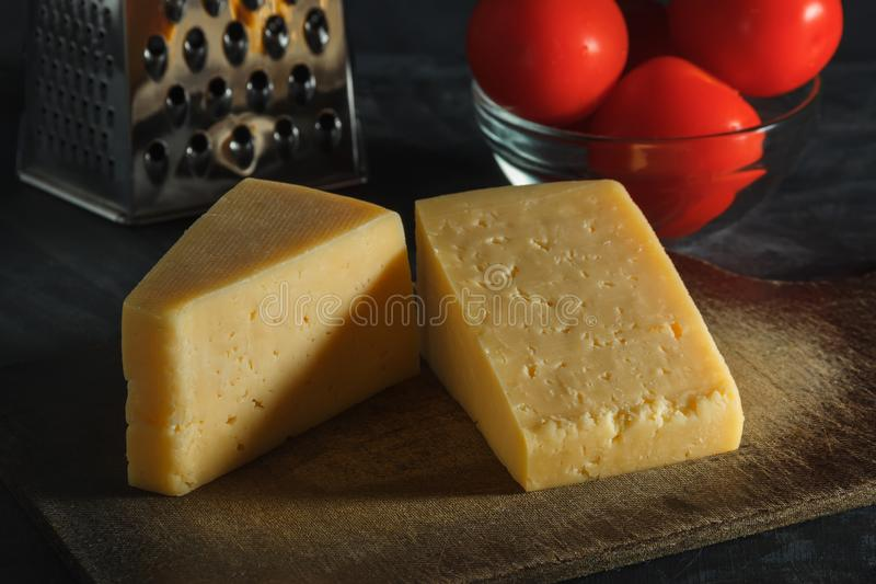 Two pieces of cheese, tomatoes and grater on a board on a dark background.  stock photo