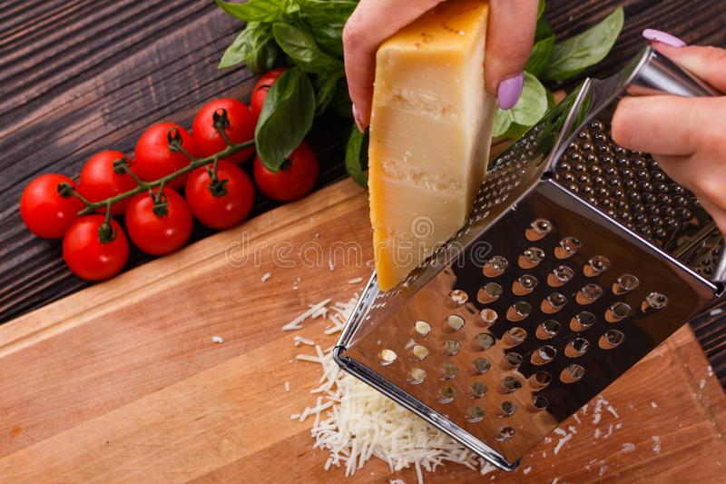 Young woman grater Parmesan cheese on a wooden board.  royalty free stock image