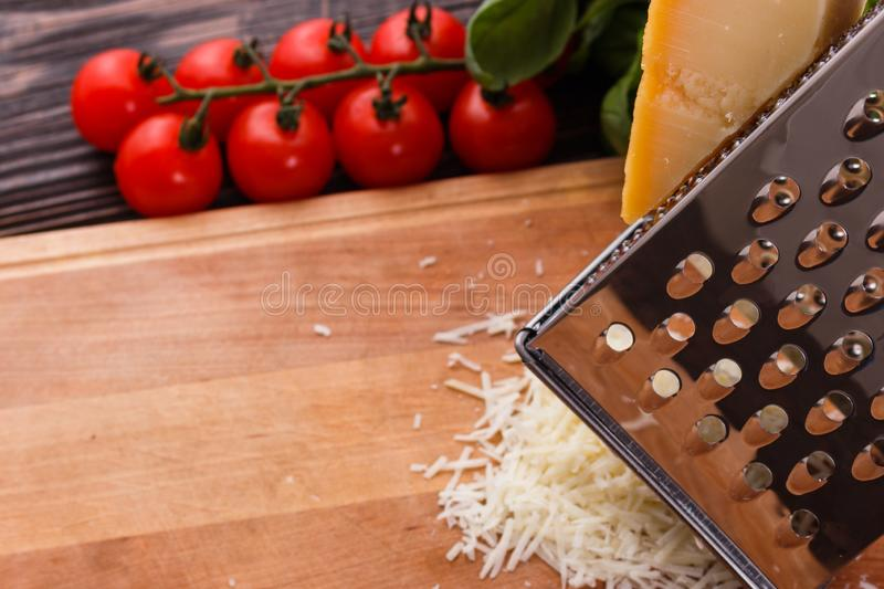 Young woman grater Parmesan cheese on a wooden board.  royalty free stock images