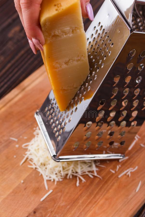 Young woman grater Parmesan cheese on a wooden board.  stock photography
