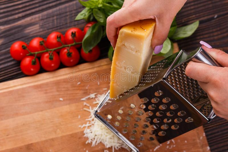 Young woman grater Parmesan cheese on a wooden board.  stock image