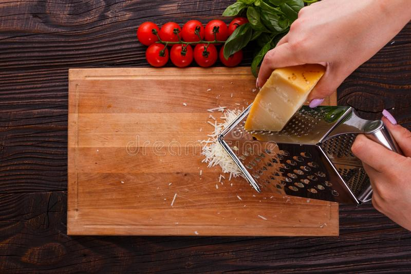 Young woman grater Parmesan cheese on a wooden board.  stock photos