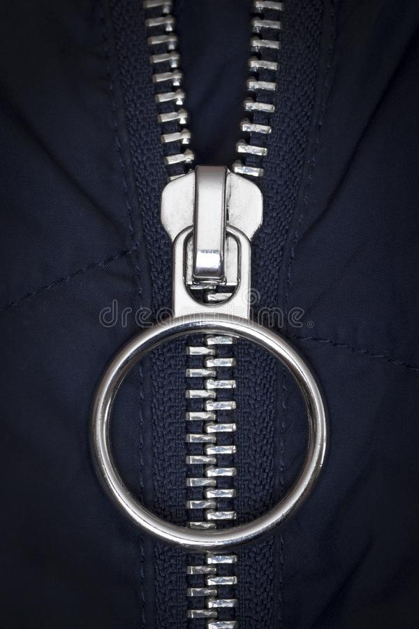 Zipper lock on the jacket. Chromed zipper lock on a blue jacket close-up stock images