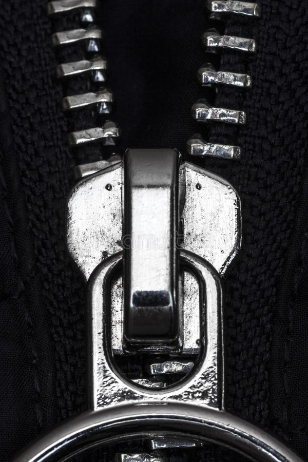 Zipper lock on the jacket. Chromed zipper lock on a blue jacket close-up stock image